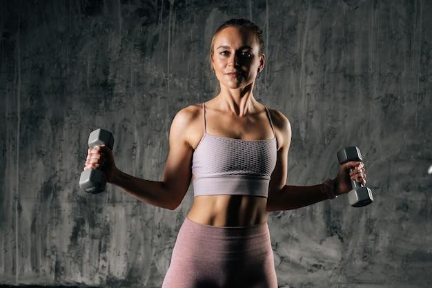 Mulher atlética jovem e musculosa com corpo lindo perfeito, vestindo roupas esportivas, malhando com halteres. mulher caucasiana de aptidão posando em estúdio com fundo cinza escuro.
