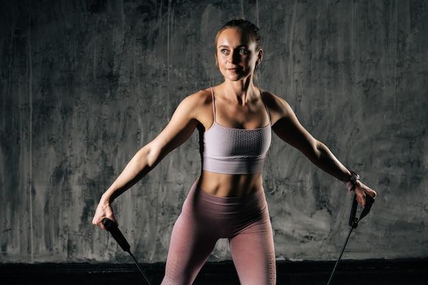 Mulher atlética jovem musculosa com corpo lindo perfeito vestindo roupas esportivas, exercitando-se com banda de resistência em pé no tapete. treinamento feminino de fitness caucasiano com expansor de alongamento no estúdio.
