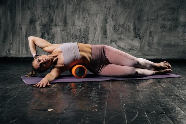 Mulher atlética jovem musculosa com corpo lindo perfeito vestindo roupas esportivas usando massageador de rolo de espuma deitado no tapete de ioga. mulher caucasiana de aptidão posando em estúdio com fundo cinza escuro.
