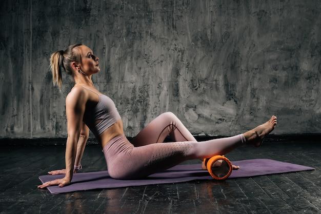 Mulher atlética jovem musculosa com corpo lindo perfeito vestindo roupas esportivas usando massageador de rolo de espuma sentado na esteira de ioga. mulher caucasiana de aptidão posando em estúdio com fundo cinza escuro.