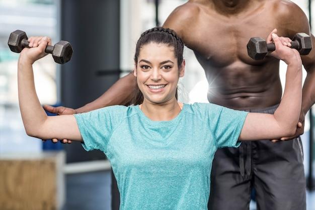 Mulher atlética, levantando pesos, ajudados pelo treinador no ginásio