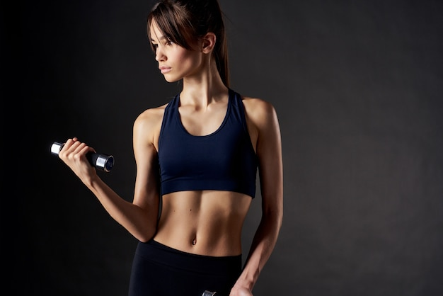 Mulher atlética magro com halteres nas mãos motivação aptidão fundo escuro