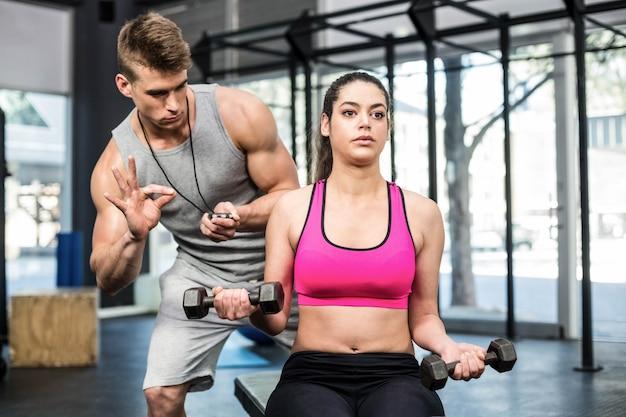 Mulher atlética malhando ajudado pelo homem de treinador no ginásio