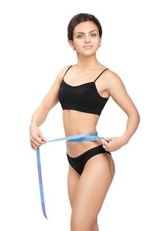 Mulher atlética medindo a cintura com a fita métrica azul após uma dieta em um branco