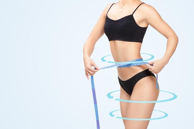 Mulher atlética medindo a cintura com a fita métrica azul após uma dieta
