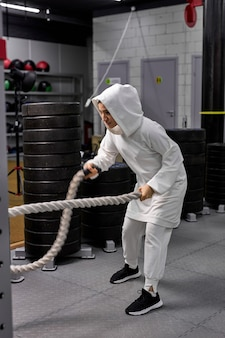 Mulher atlética muçulmana malhando com cordas na cruz fit ginásio copyspace confiança motivação esportes estilo de vida atividade passatempo saudável poderoso conceito de treinamento de feminilidade. vista lateral