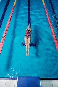 Mulher atlética nadando nas costas na piscina
