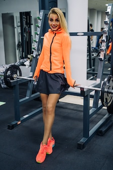 Mulher atlética no dia das bruxas. fêmea de aptidão com arte corporal no rosto. celebração no ginásio. retrato de corpo inteiro.