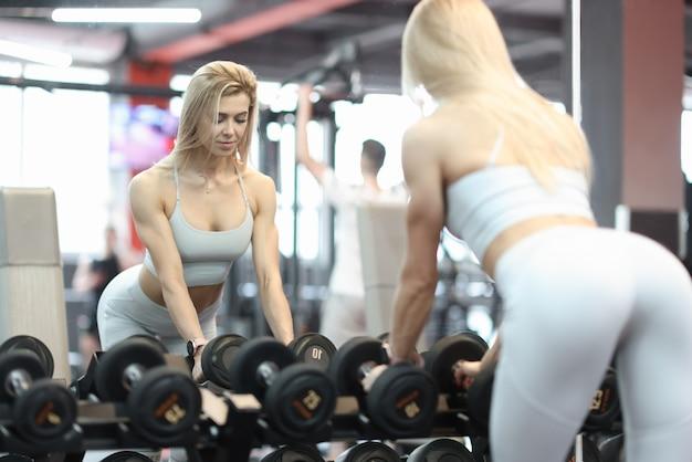 Mulher atlética pega halteres no ginásio