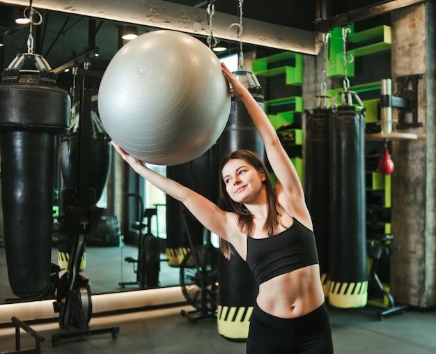 Mulher atlética proposital no sportswear praticando com fitball nas mãos no ginásio