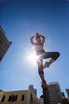 Mulher atlética que faz ioga no poste de amarração