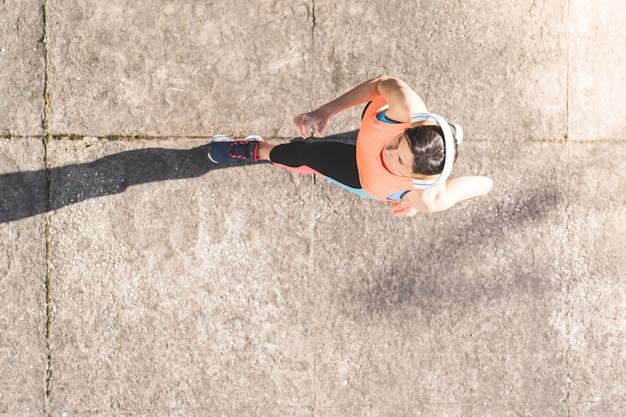 Mulher atlética que movimenta-se no pavimento.