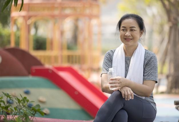 Mulher atlética sênior bebe água de uma garrafa depois de correr no parque.