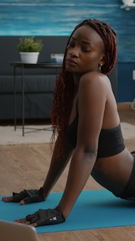 Mulher atlética slim fit praticando esporte durante exercícios matinais de ioga
