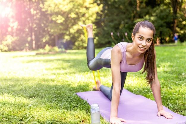 Mulher atlética sorridente está fazendo yoga