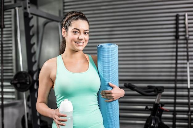 Mulher atlética sorrindo para a câmera no ginásio crossfit