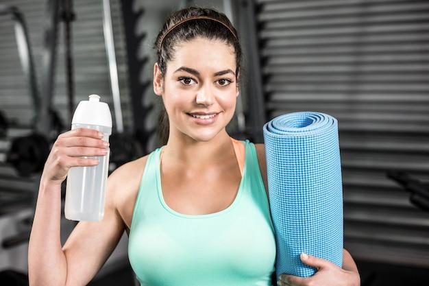 Mulher atlética sorrindo para a câmera no ginásio