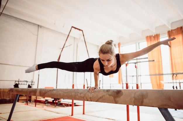 Mulher atlética treinando na trave de equilíbrio