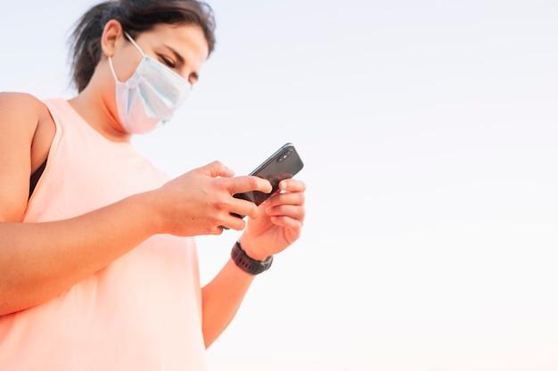Mulher atlética usando seu smartphone com máscara facial ao ar livre