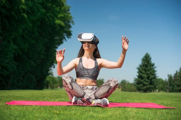 Mulher atlética, usando um óculos de realidade virtual ao ar livre