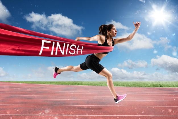 Mulher atlética vai além da fita vermelha na chegada de uma corrida