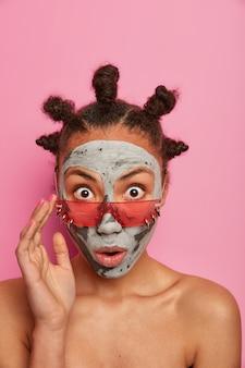 Mulher atônita e emocional encara com os olhos bem abertos, usa óculos de sol da moda, aplica máscara facial de beleza, posa sem camisa em ambientes internos contra uma parede rosada. tratamentos faciais, cocept cuidados com a pele