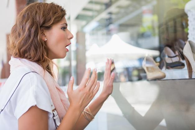 Mulher atônita, tocando a janela com uma mão