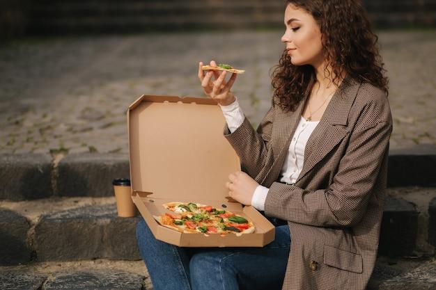 Mulher atraente abrindo caixa de pizza e comendo pizza vegana ao ar livre