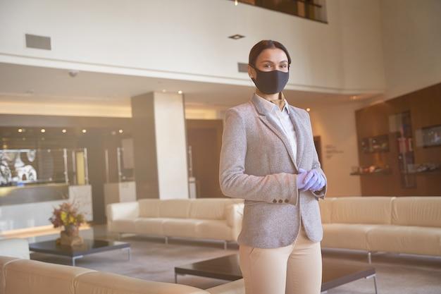 Mulher atraente administradora de hotel em pé em um corredor vazio sozinha com sofás confortáveis ao fundo