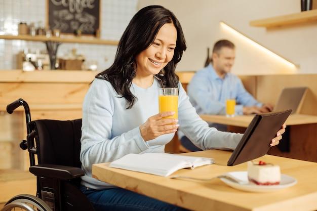Mulher atraente alegre com deficiência sentada em uma cadeira de rodas e bebendo suco enquanto trabalhava em seu tablet em um café e um homem sentado ao fundo