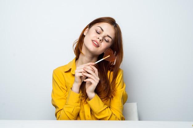 Mulher atraente alegre com um pirulito em forma de coração se senta à mesa.