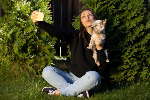 Mulher atraente, alegre, morena, com cabelos longos, vestida com um capuz preto e emocionalmente fazendo selfies de beijo com cachorro yorkshire no fundo do tui verde