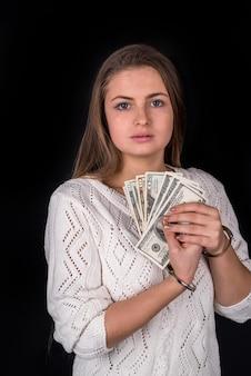 Mulher atraente algemada com suborno isolado no preto