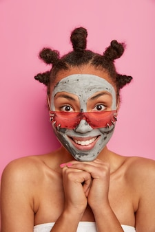 Mulher atraente aplica máscara de lama no rosto, sorri gentilmente, tem dentes brancos perfeitos, pele bem cuidada, usa óculos escuros rosados, mostra os ombros nus, enrolada em toalha de banho, passa por procedimentos de beleza