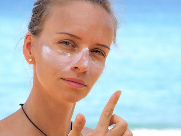 Mulher atraente aplica protetor solar no rosto em uma praia tropical.