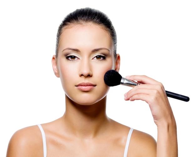 Mulher atraente aplicando aspereza no rosto bonito - isolado no branco