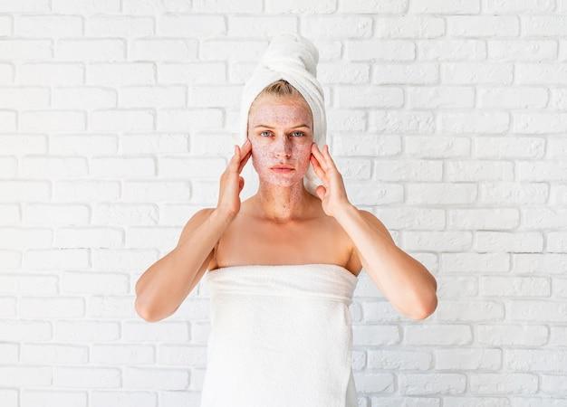 Mulher atraente aplicando esfoliante na pele. conceito de limpeza facial