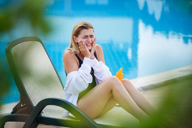 Mulher atraente aplicando protetor solar no rosto à beira da piscina. fator de proteção solar de férias