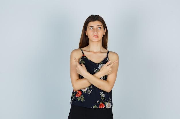Mulher atraente apontando para cima e mordendo o lábio inferior na blusa e olhando com problemas, vista frontal.