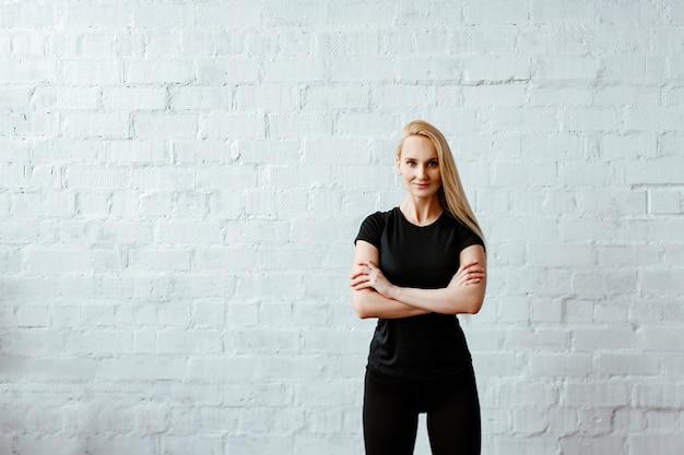Mulher atraente aptidão loira jovem em um top preto posa contra uma parede de tijolos brancos com os braços cruzados sobre o peito