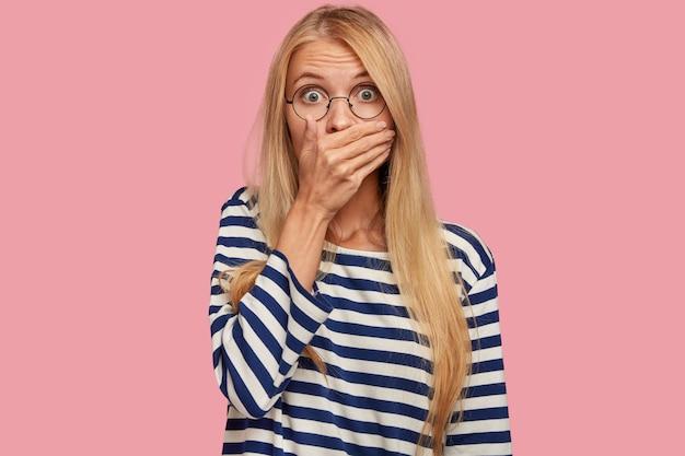 Mulher atraente atônita com cabelo loiro cobre a boca em choque ao ouvir notícias repentinas