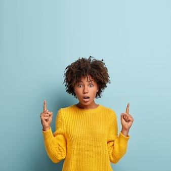Mulher atraente atordoada aponta o dedo indicador para cima, mostra um espaço em branco para conteúdo publicitário, respirou fundo, impressionada com algo assustador, usa um macacão amarelo, posa sobre a parede azul. conceito omg