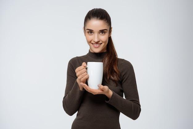 Mulher atraente, bebendo chá, segurando xícara