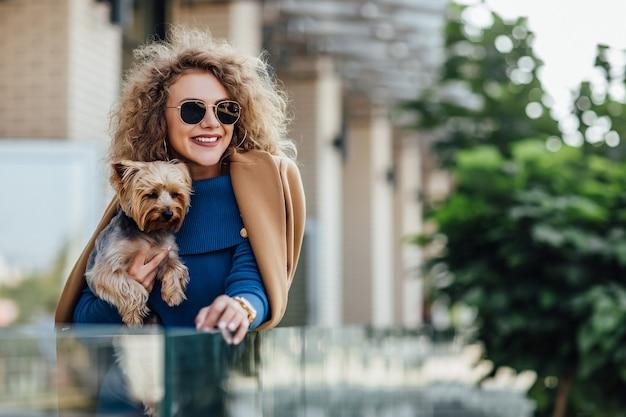 Mulher atraente bem sucedida segurando yorkshire terrier.