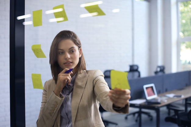 Mulher atraente busness postar adesivos em vidro no escritório e escrevendo sobre eles.