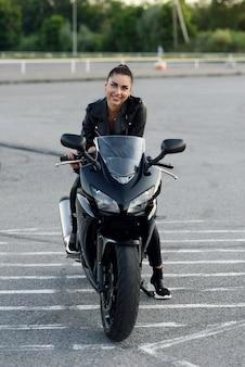 Mulher atraente, cabelos compridos em jaqueta de couro preta e calças no estacionamento ao ar livre com moto esportes elegante ao pôr do sol.