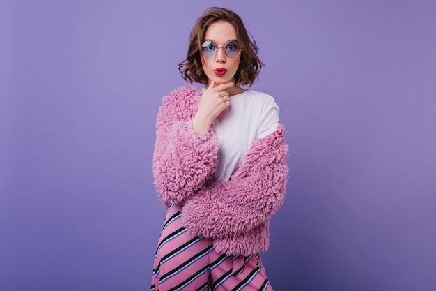 Mulher atraente caucasiana em trajes brilhantes, com expressão de surpresa. retrato interior de modelo feminino encaracolado refinado com casaco de pele rosa.