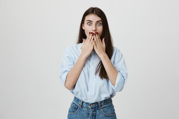 Mulher atraente chocada ofegando, tapando a boca sem palavras