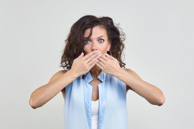Mulher atraente cobrindo a boca com as mãos