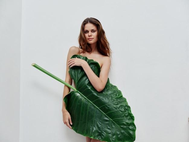 Mulher atraente cobrindo corpo nu com luz de fundo verde